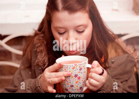 Teenage girl blowing on mug of coffee outdoors - Stock Photo
