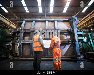 Engineers inspecting engineering drawings in factory, rear view - Stock Photo