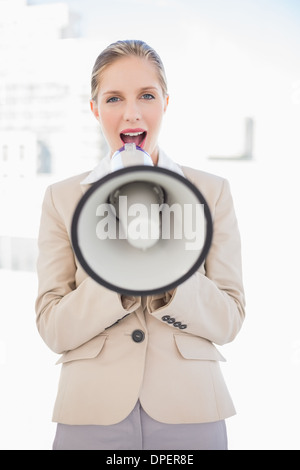Blonde businesswoman shouting in megaphone - Stock Photo