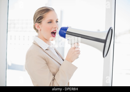 Energetic blonde businesswoman shouting in megaphone - Stock Photo