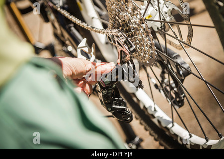 Man fixing mountain bike, close up - Stock Photo
