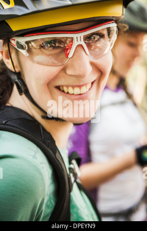 Portrait of female cyclist wearing cycling glasses - Stock Photo