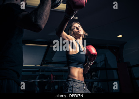 Female boxer punching instructor's punch shield - Stock Photo