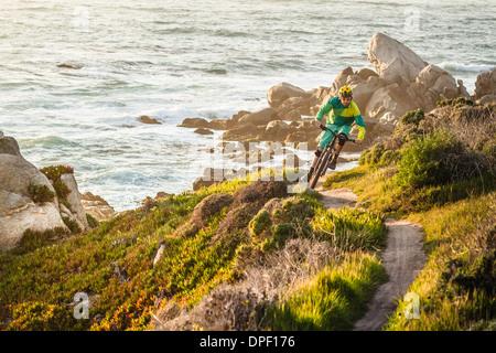 Mountain biker riding up coastal path, Monterey Bay area, California, USA - Stock Photo