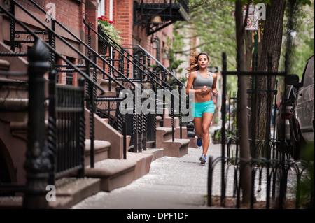 Woman jogging on sidewalk - Stock Photo
