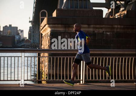 Man jogging on sidewalk - Stock Photo