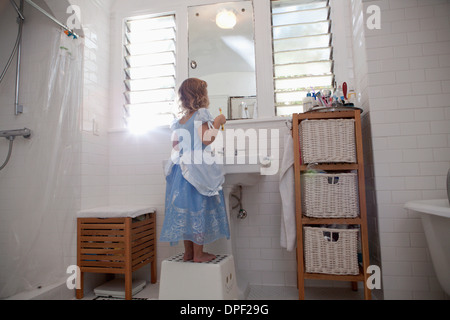 Female toddler standing on step cleaning teeth - Stock Photo