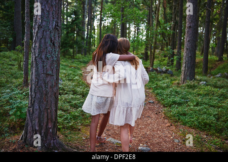 Teenage girls with arms around each other forest - Stock Photo