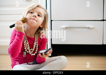 Young girl sitting on kitchen floor with make up - Stock Photo
