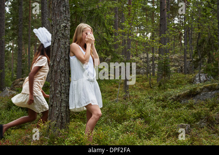 Teenage girls playing hide and seek in forest - Stock Photo