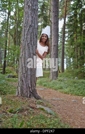 Teenage girl wearing white hat by tree in forest - Stock Photo