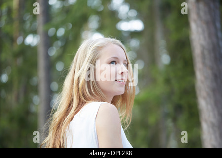 Portrait of teenage girl with long blonde hair looking away - Stock Photo
