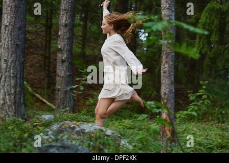 Teenage girl running in forest - Stock Photo