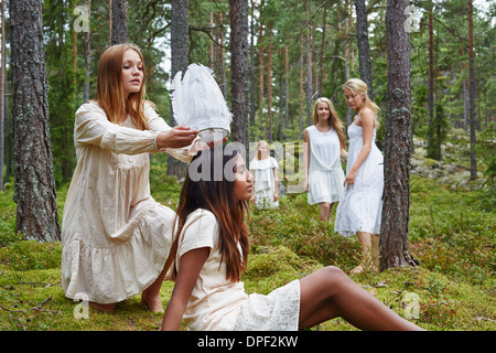 Teenage girl putting white hat on friend in forest - Stock Photo