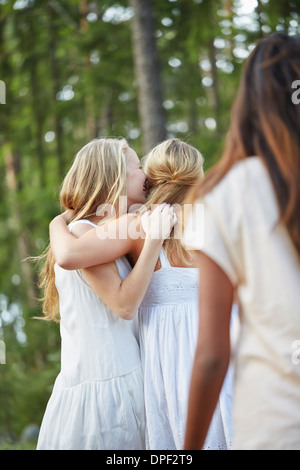 Teenage girls with arm around each other in forest - Stock Photo