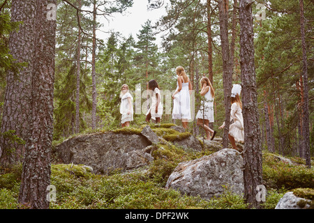 Teenage girls walking over rocks in forest - Stock Photo