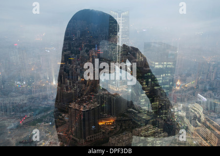 Businesswoman using smartphone and Hong Kong cityscape, composite image - Stock Photo