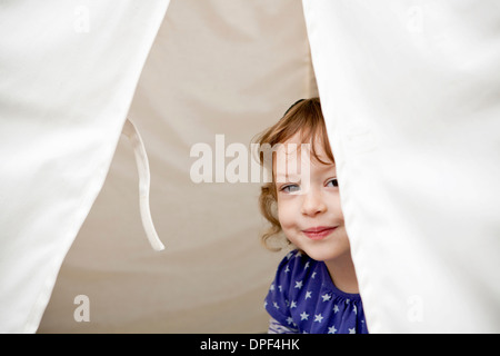 Portrait of female toddler peeking out of tent - Stock Photo