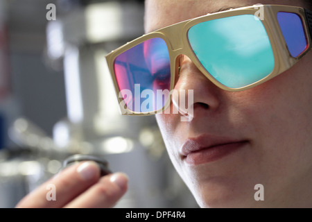 Close up of female scientist examining sample in laboratory - Stock Photo