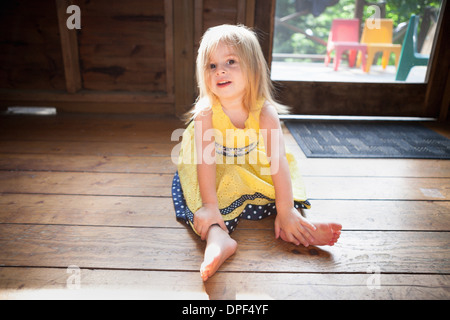 Female toddler sitting on wooden floor - Stock Photo