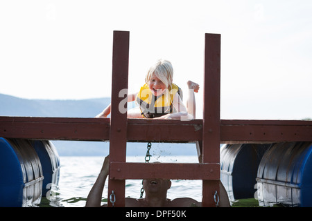 Father hiding in lake from toddler daughter, Silver Bay, New York, USA - Stock Photo
