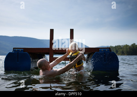 Father and toddler daughter playing in lake, Silver Bay, New York, USA - Stock Photo