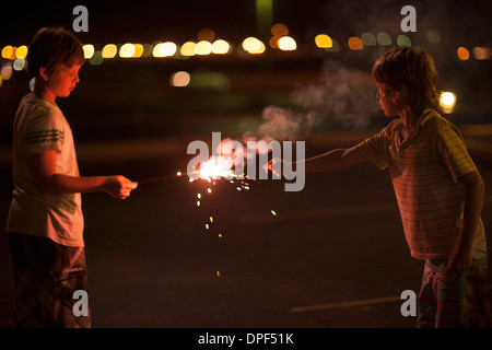 Two boys playing with sparklers on 4th July - Stock Photo