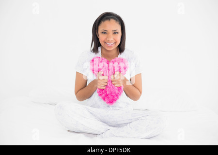 Content young dark haired model cuddling a heart-shaped pillow - Stock Photo