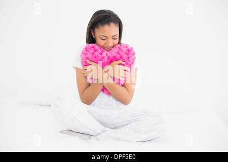 Peaceful young dark haired model cuddling a heart-shaped pillow - Stock Photo