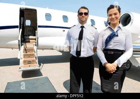 Stewardess And Pilot Standing Against Private Jet - Stock Photo