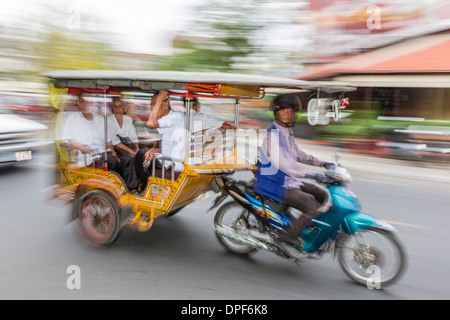 Motion blur image of a tuk-tuk in the capital city of Phnom Penh, Cambodia, Indochina, Southeast Asia, Asia - Stock Photo