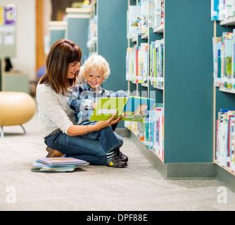 Boy And Teacher Reading Book By Bookshelf - Stock Photo