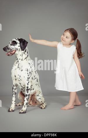 Studio portrait of female toddler and dalmatian dog - Stock Photo