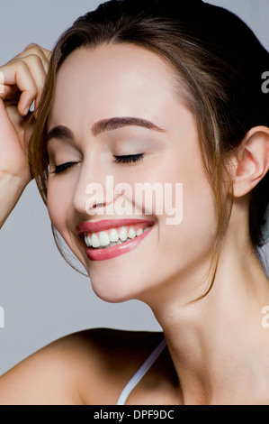 Studio portrait of young smiling woman with eyes closed - Stock Photo