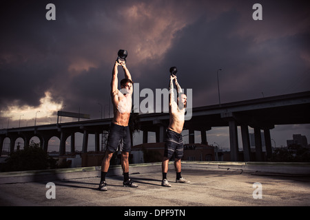 Two men training with kettlebells on gymnasium rooftop - Stock Photo