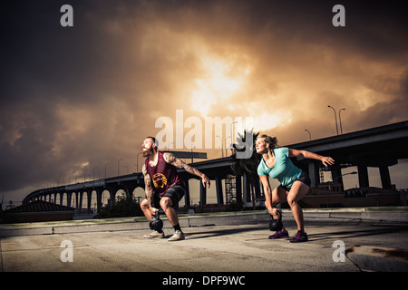 Man and woman training with kettlebells on gymnasium rooftop - Stock Photo