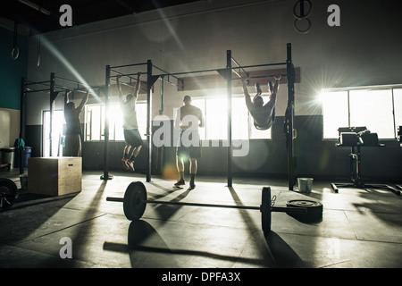 Three men training on exercise bar in gymnasium - Stock Photo