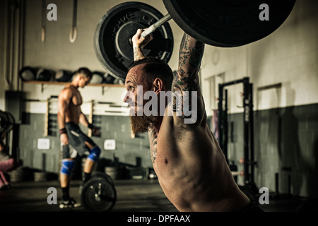 Mid adult man lifting barbell in gymnasium - Stock Photo