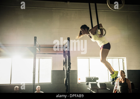 Young woman on gymnasium rings watched by trainer - Stock Photo