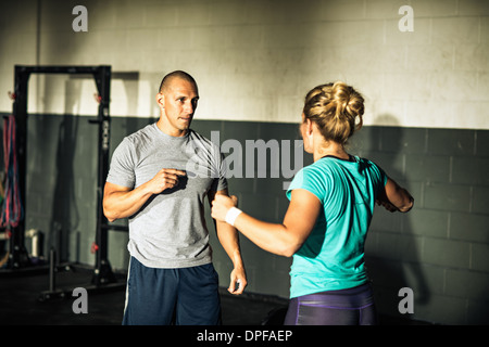 Trainer mentoring young woman in gymnasium - Stock Photo