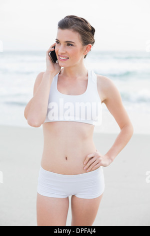 Thoughtful slim brown haired model in white sportswear making a phone call - Stock Photo