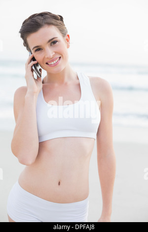 Pleased slim brown haired model in white sportswear making a phone call - Stock Photo