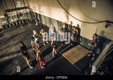 Trainer talking to fitness group in gym - Stock Photo