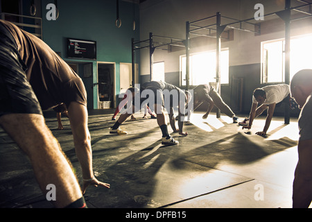 Fitness group training together in gym - Stock Photo