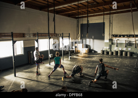 Fitness class warming up together in gym - Stock Photo