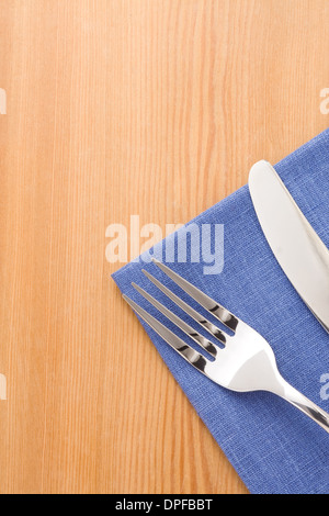silver fork and knife as utensils at napkin on wooden background - Stock Photo