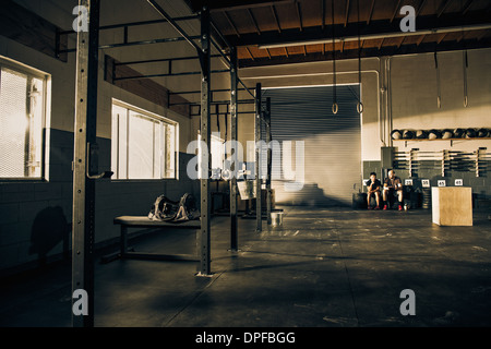 Two men taking a break from training in gymnasium - Stock Photo