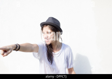 Young woman with attitude pointing finger - Stock Photo