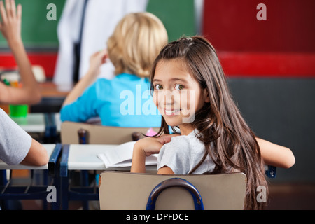Schoolgirl Sitting At Desk In Classroom - Stock Photo