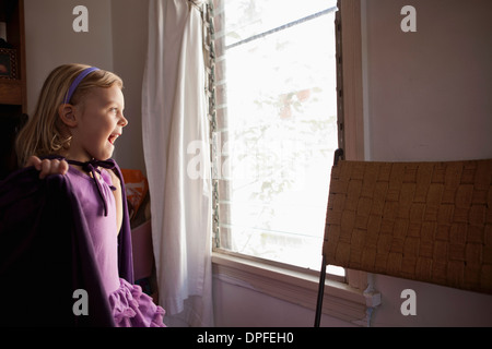 Portrait of young girl looking out of window - Stock Photo